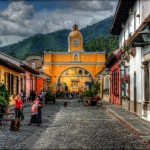 Nice cobblestone stree in Antigua, Guatemala.  ISO 100, 56mm, f8, 1/250. Tonemapped in Photomatix Details Enhancer. Nik Pro Contrast, Tonal Contrast and Viveza to brighten church, darken coblestone and make the blue bluer in the sky.